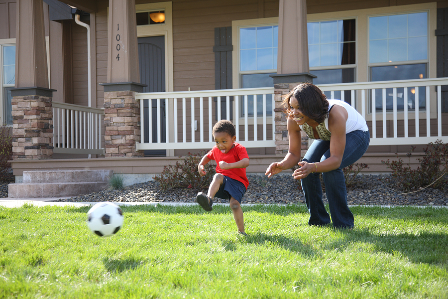 Mom And Son Playing Soccer In The Front Yard.