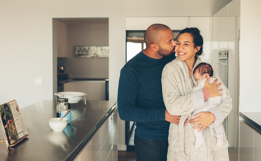 Loving Young Couple With Their Newborn Baby Boy In Kitchen. Beautiful Young Family Of Three In Morning In Kitchen.