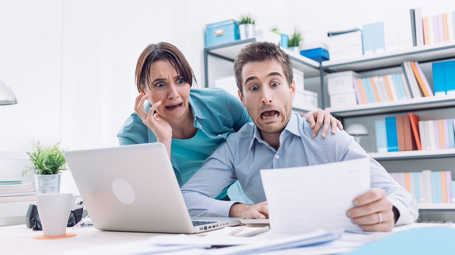 Stressed Young Couple Checking Bills Taxes And Bank Account Balance They Are Panicking Debt And Cost Of Living Concept