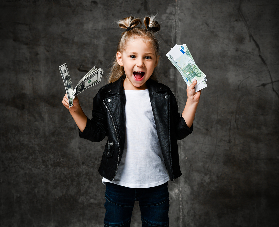 Lucky Rich Kid Girl Millionaire Is Holding In Hands, Shaking, Waving Us Bundles Of Money Euro Hundreds Dollars Cash Bills Happy Screaming On Dark Concrete Wall Background