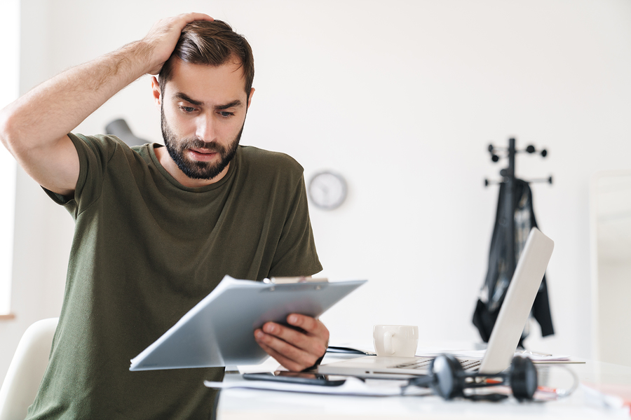 Image Of Perplexed Handsome Man Reading Documents And Holding Clipboard While Sitting At Desk In Bright Office