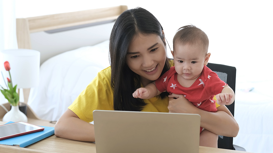 Beautiful Business Asian Mom Is Using A Laptop And Smiling While Spending Time With Her Cute Baby At Home. Young Mother On Maternity Leave Trying To Freelance By The Desk With Toddler Child.